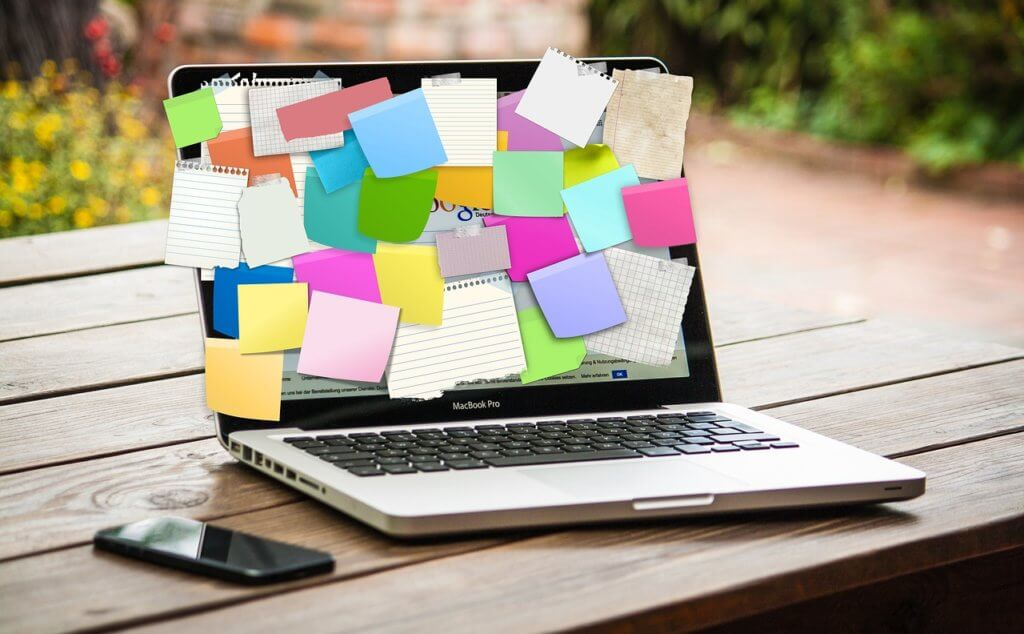 computer with sticky notes outside on a table